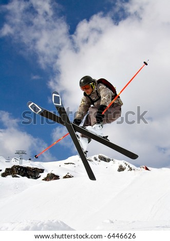 Young Skier Jumping extreme high over the snow - stock photo