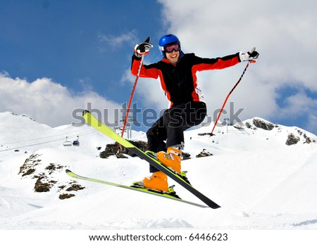 Young Skier Jumping high over the snow - stock photo