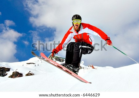 Young Skier Jumping high over the snow, showing tongue - stock photo