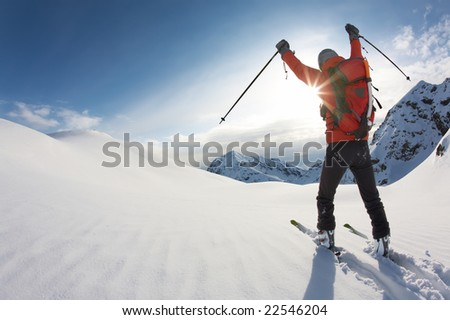 Young skier reaches his arms up over a snowy mountain landscape, italian alps; horizontal frame