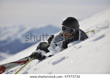 young skier relaxing in snow and looking mountain range at beautiful sunny winter day - stock photo