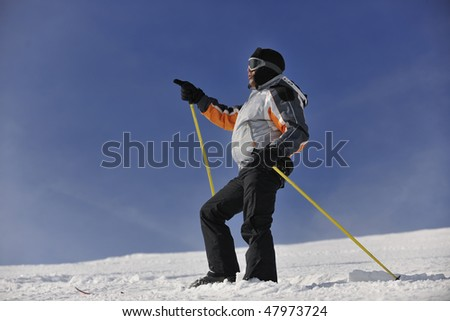 young skier relaxing, with hand pointing and  looking mountain range at beautiful sunny winter day - stock photo