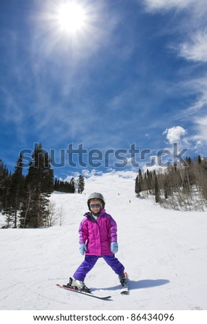Young Skier skiing down a perfect ski run - stock photo