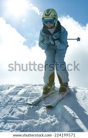 Young skier standing on top of hill, looking at camera, full length portrait