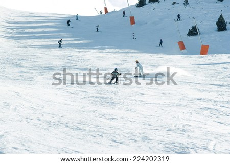 Young skiers on ski slope, in the distance - stock photo