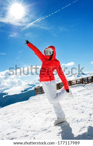 young skiing girl or woman posing against winter sunny landscape