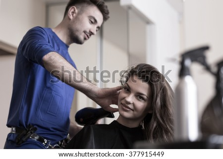 Young skilled man haidresser using a hairdryer - stock photo