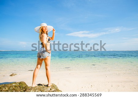 Young skinny caucasian woman with tan stays on the rock against blue sky and pure ocean water on background. Travel, vacation, paradise concept, copyspace - stock photo