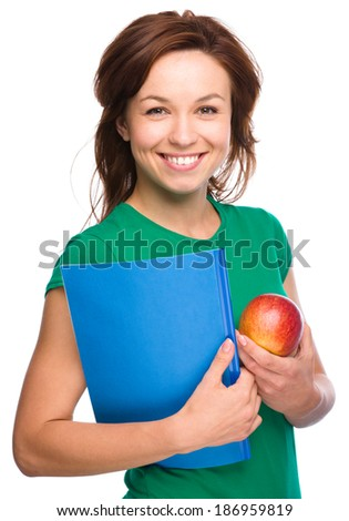 Young skinny student girl is holding exercise book and apple, isolated over white