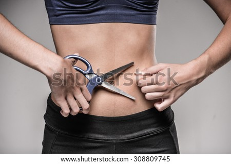 Young skinny woman cuts her belly by scissors. Weight loss concept. - stock photo