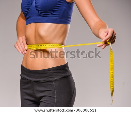 Young skinny woman is measuring her waist during diet. - stock photo