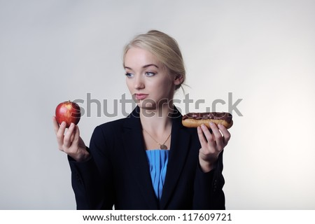 young skinny women not sure if she should eat a chocolate cream cake or a healthy apple
