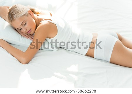 Young sleeping woman at bedroom - stock photo