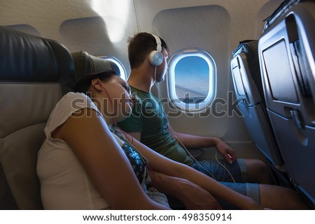 Young sleeping woman lying on the male shoulder, both wearing headphones, while traveling by airplane