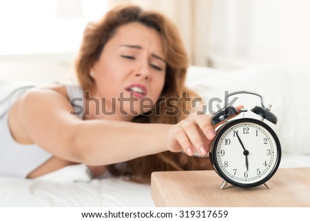 Young sleepy woman trying to turn off the alarm clock. Early morning waking up. - stock photo