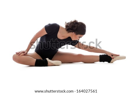 Young slender ballerina doing stretching in studio - stock photo