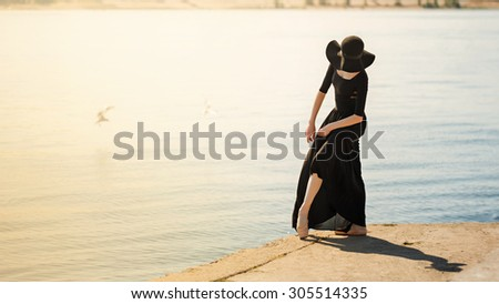 Young slender ballerina in black dress and hat dancing beautifully on the river bank. Summer day. The concept modern ballet. Performance on the street. Minimalism. Warm toning. Soft focus