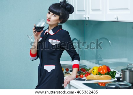 Young slender girl is drinking wine in the kitchen. The girl is preparing dinner. Household chores. - stock photo
