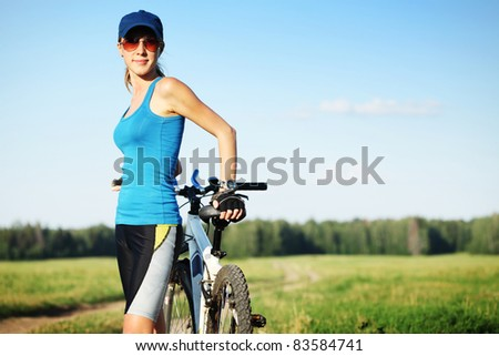 Young slender woman in red glasses standing by bicycle and looking to a camera - stock photo