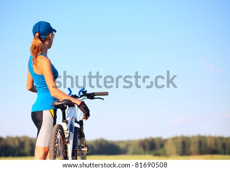 Young slender woman standing by bicycle and looking to a sky - stock photo