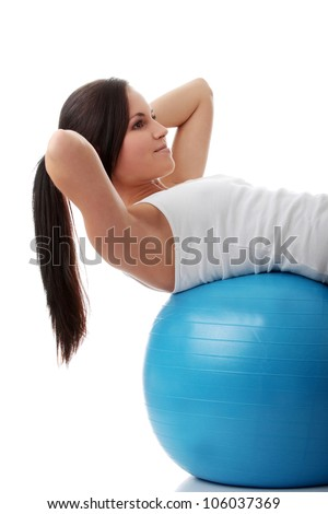 Young, slim and athletic woman doing fitness and exercise with blue ball. Fit girl doing sit-ups and wearing white, sport t-shirt.  Isolated on the white background. - stock photo