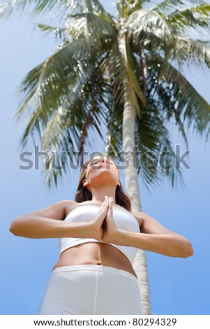 Young slim and strong  woman doing yoga against palm tree - stock photo