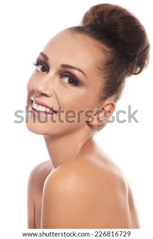 Young slim attractive smiling woman with stylish hair bun over white background - stock photo