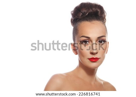 Young slim attractive woman with stylish hair bun and red lipstick over white background - stock photo