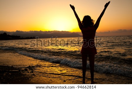 Young slim girl is enjoying the freedom. Sunset and sea - stock photo