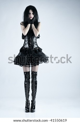 Young slim goth woman. On soft blue background. - stock photo