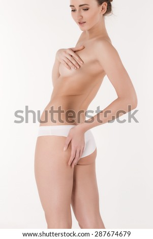 Young, slim, healthy and beautiful woman in white lingerie isolated on the white background. hips and waist girl shot closeup. girl's hand covers the chest - stock photo