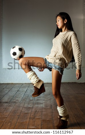 Young slim japanese woman playing toy football.