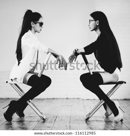 Young slim japanese women sitting on chairs. - stock photo