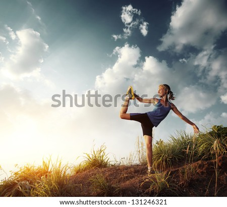 Young slim lady doing stretching exercises on a rural path with grass and cloudy sky on the background - stock photo