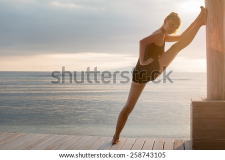 Young slim lady doing yoga stretching exercises on a beach with sunset over Bali in the background - stock photo