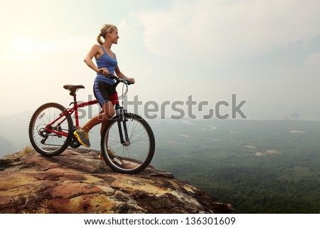 Young slim lady standing on top of a mountain with bicycle and enjoying valley view - stock photo