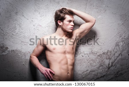 Young slim man posing topless on a gray wall