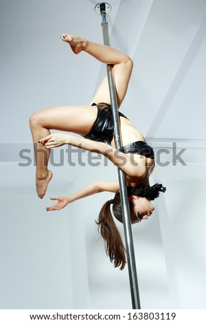 Young slim pole dance woman in dance studio