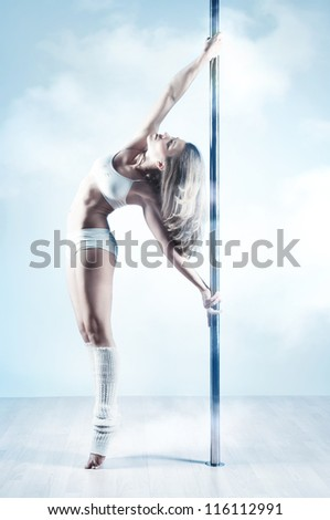 Young slim pole dance woman. Soft blue and white colors. - stock photo
