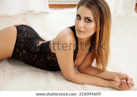 Young slim sexy and attractive brunette woman in black lingerie against the window - stock photo