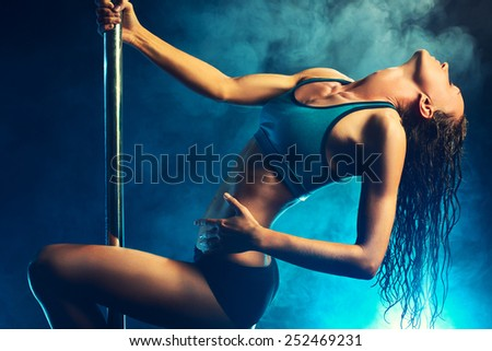 Young slim sexy brunette pole dance woman. Smoke effect on background. - stock photo
