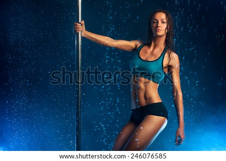 Young slim sexy brunette pole dance woman. Water rain effect. - stock photo