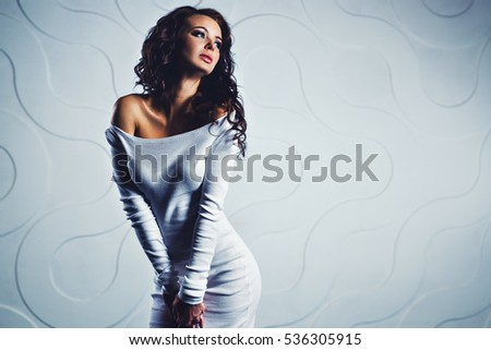 Young slim sexy brunette woman in white dress portrait in modern interior