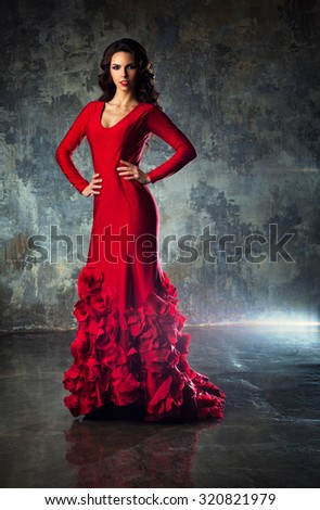 Young slim sexy fashion woman in long red dress standing on stone wall background. - stock photo
