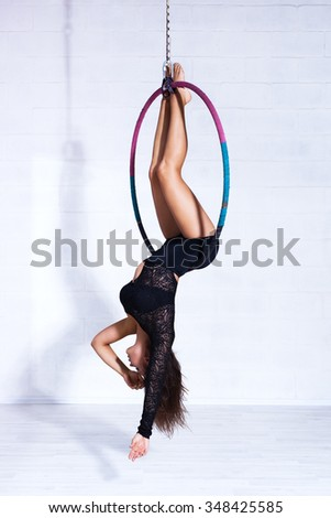 Young slim sports woman in black clothing hanging on ring upside down - stock photo