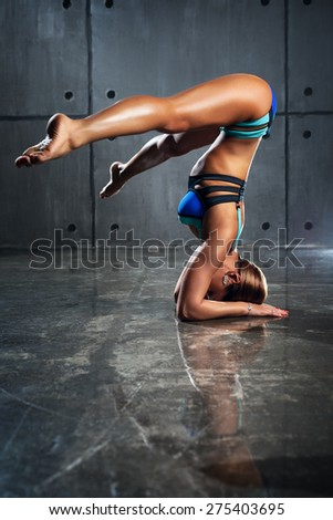 Young slim sports woman standing upside down on stone wall background. - stock photo