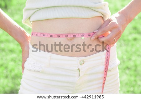Young slim sporty woman with with measuring tape outdoor - stock photo