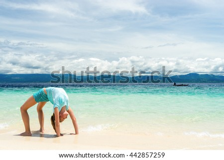 young slim teen girl do gymnastic exercise at white sand beach of tropical sea under blue sky - stock photo