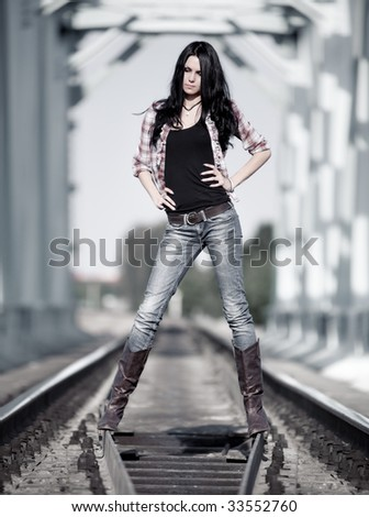 Young slim woman at the railways. - stock photo