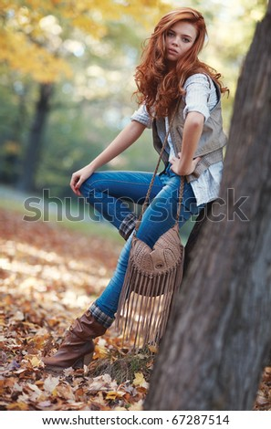 Young slim woman autumn portrait. Camera angle view. - stock photo